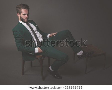 Business fashion man wearing green suit with white shirt black and tie. Sitting on wooden chair. Studio shot against grey. - stock photo