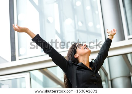 Business female executive success. Successful and blissful woman outside corporate building. Successful and happy hispanic brunette businesswoman with arms up.