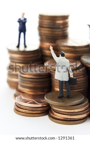 Business figures on stacks of coins - stock photo