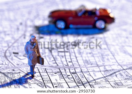 Business figurine and toy car on a map - stock photo