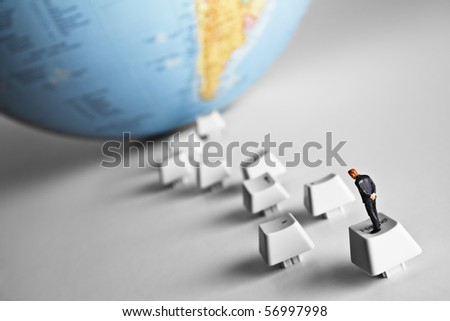 Business figurine placed on computer keys that lead to an earth globe - stock photo