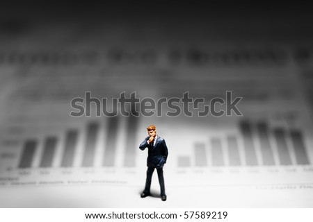 Business figurine standing in front of a graph - stock photo