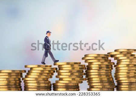 Business figurine walking across stacks of coins