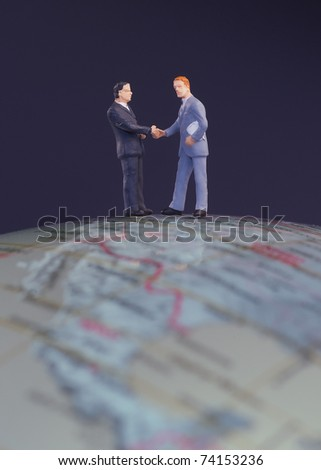 Business figurines handshake on international globe - stock photo