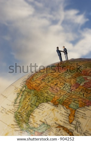 Business figurines on earth globe shaking hands - stock photo