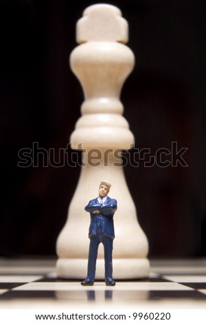 Business figurines placed on chessboard with chess pieces - stock photo