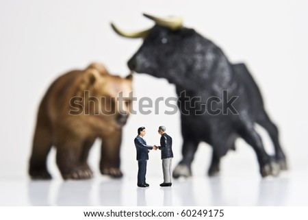 Business figurines shaking hands placed in front of bull and bear figurines. - stock photo