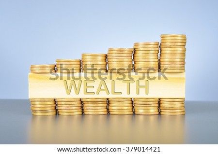 Business finance concept; golden coin graph and piece of wood with carved word wealth.