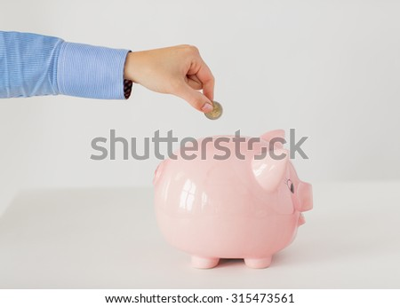 business, finance, investment, money saving and budget concept - close up of hand putting coin into piggy bank - stock photo
