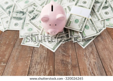business, finance, investment, saving and corruption concept - close up of dollar cash money and piggy bank on wooden table background - stock photo