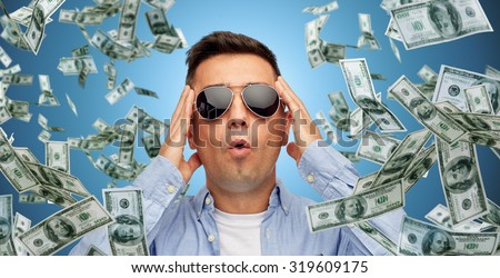 business, finance, luck, fortune and people concept - face of scared or surprised middle aged latin man in sunglasses over blue background with heap of falling dollar money - stock photo