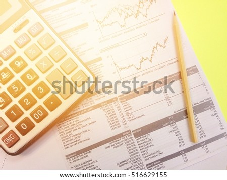 Business, finance or work day background concept : Top view of calculator, pencil and company summary data charts on yellow background