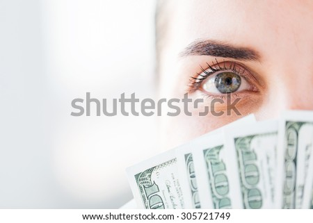 business, finance, saving, banking and people concept - close up of woman hiding her face behind us dollar money fan - stock photo