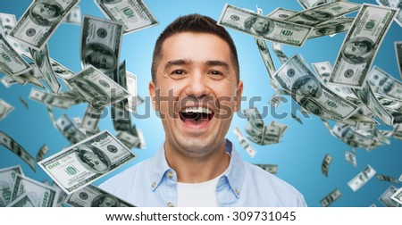 business, finance, success, emotions and people concept - laughing man over blue background with heap of falling dollar money - stock photo