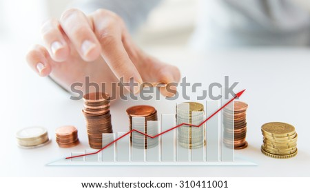 business, finances, people and money saving concept - close up of female hand putting euro coins into columns and growing chart