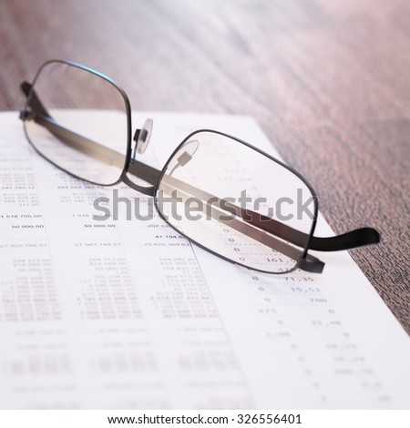 Business financial report and glasses on a table close-up