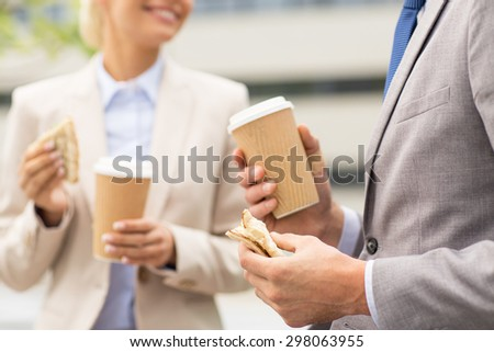 business, food, drink, communication and people concept - close up of smiling businessmen with coffee cups and sandwiches having lunch and talking outdoors