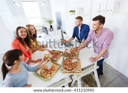 business, food, lunch and people concept - happy international business team eating pizza in office - stock photo
