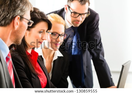 Business - Four professionals in office in business attire looking at laptop screen working together - stock photo