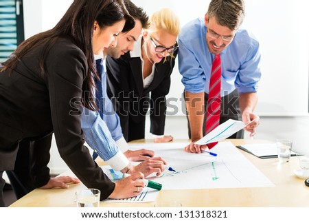 Business - Four professionals in the office in business clothes when planning a strategy for the future of the business - stock photo