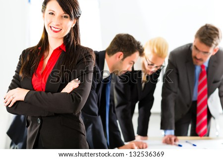 Business - Four professionals in the office in business clothes when planning a strategy for the future of the business, a woman smiles into the camera - stock photo