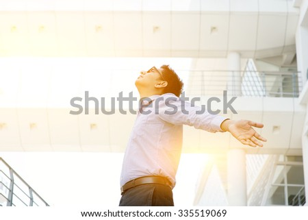 Business freedom concept. Asian businessman arms outstretched enjoying the morning breeze, morning sunlight and modern office as background. - stock photo