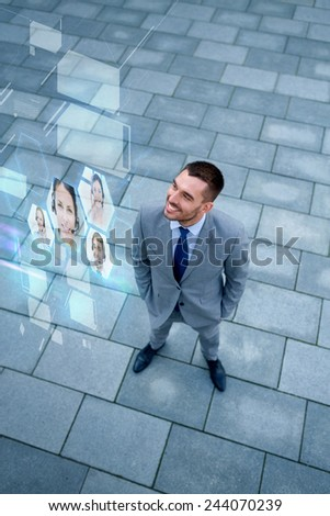 business, future technology and people concept - young smiling businessman with virtual screens using video chat outdoors from top