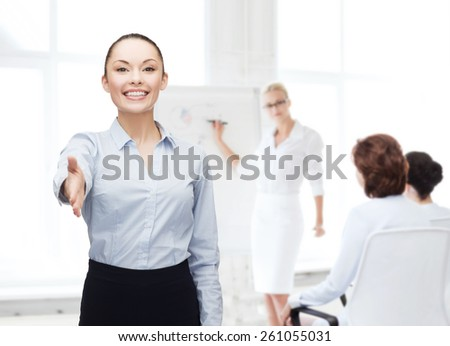 business, gesture and education concept - friendly young smiling businesswoman with opened hand ready for handshake - stock photo
