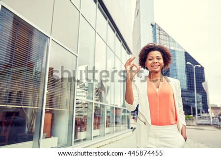 business, gesture and people concept - young smiling african american businesswoman in city showing ok hand sign - stock photo