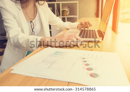 Business Girl analyzing investment charts with laptop vintage tone - stock photo