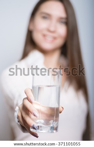 Business girl gives a glass of water, isolated on background