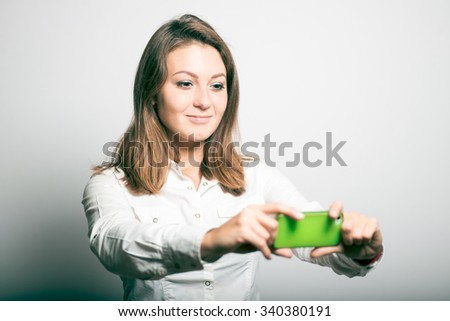 business girl photographed on a mobile phone. studio photo on a gray background - stock photo