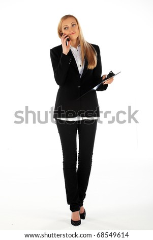 Business girl walking and talking on mobile phone - stock photo