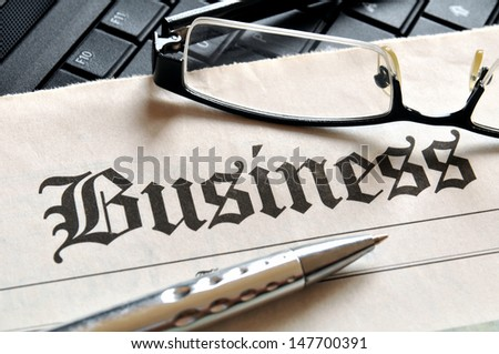 Business, glasses and ball pen on newspaper headline - stock photo