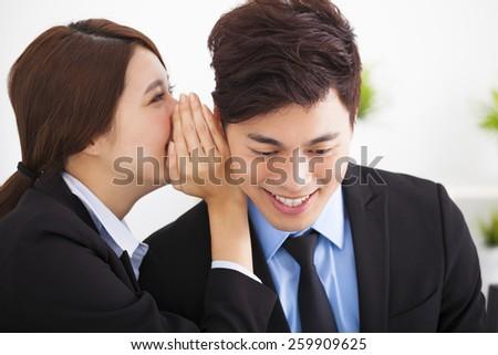 business gossip between businesswoman and businessman - stock photo