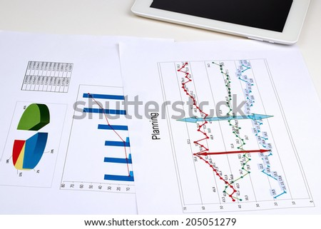 Business graph analysis report. Digital tablet beside - stock photo