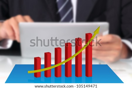 Business graph and businessman using digital tablet