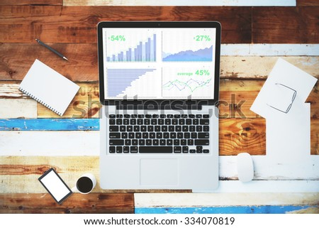 Business graph on laptop screen with blank smartphone and other accesories on wooden table, mock up - stock photo