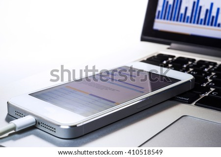Business graph on smartphone with laptop Screen in modern lifestyle.business  and  technology concept
