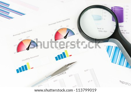 Business graph printed on the white paper with a magnifier on it - stock photo