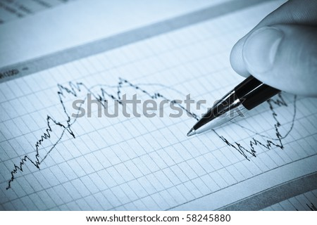 Business graph with hand of man with pen - stock photo