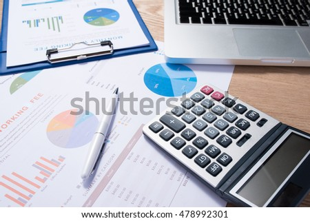 Business graphs and charts on a wooden desk with a calculator, coffee mug and pen
