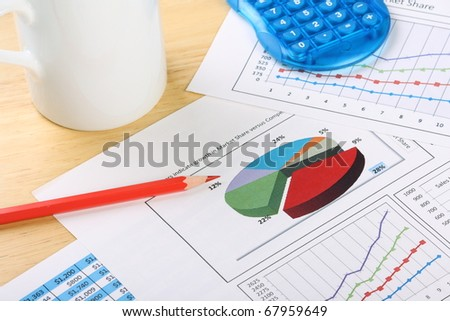 Business graphs and charts on a wooden desk with a calculator, coffee mug and red pencil
