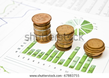 Business graphs and charts with stacks of coins - stock photo