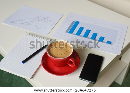 business graphs and diagrams, note book, pen, cellphone and red cup of coffee on the table