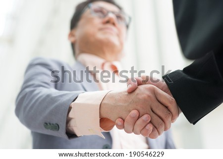 Business greeting, Asian businessmen handshaking. Chinese CEO boss. Focus on hands. Modern  office building architecture background.