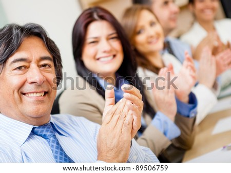 Business group applauding celebrating their success at the office - stock photo