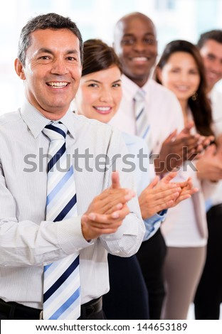 Business group celebrating their success at the office applauding - stock photo