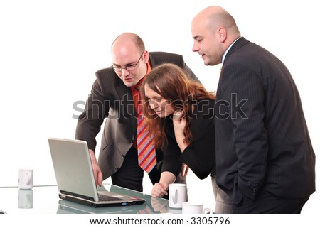 Business group looking at a computer on a glass table with coffee cups. - stock photo