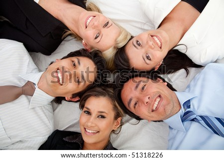 Business group lying on the floor with their heads together - stock photo